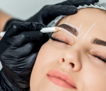 Markup with pencil on eyebrows of young woman while permanent make up.